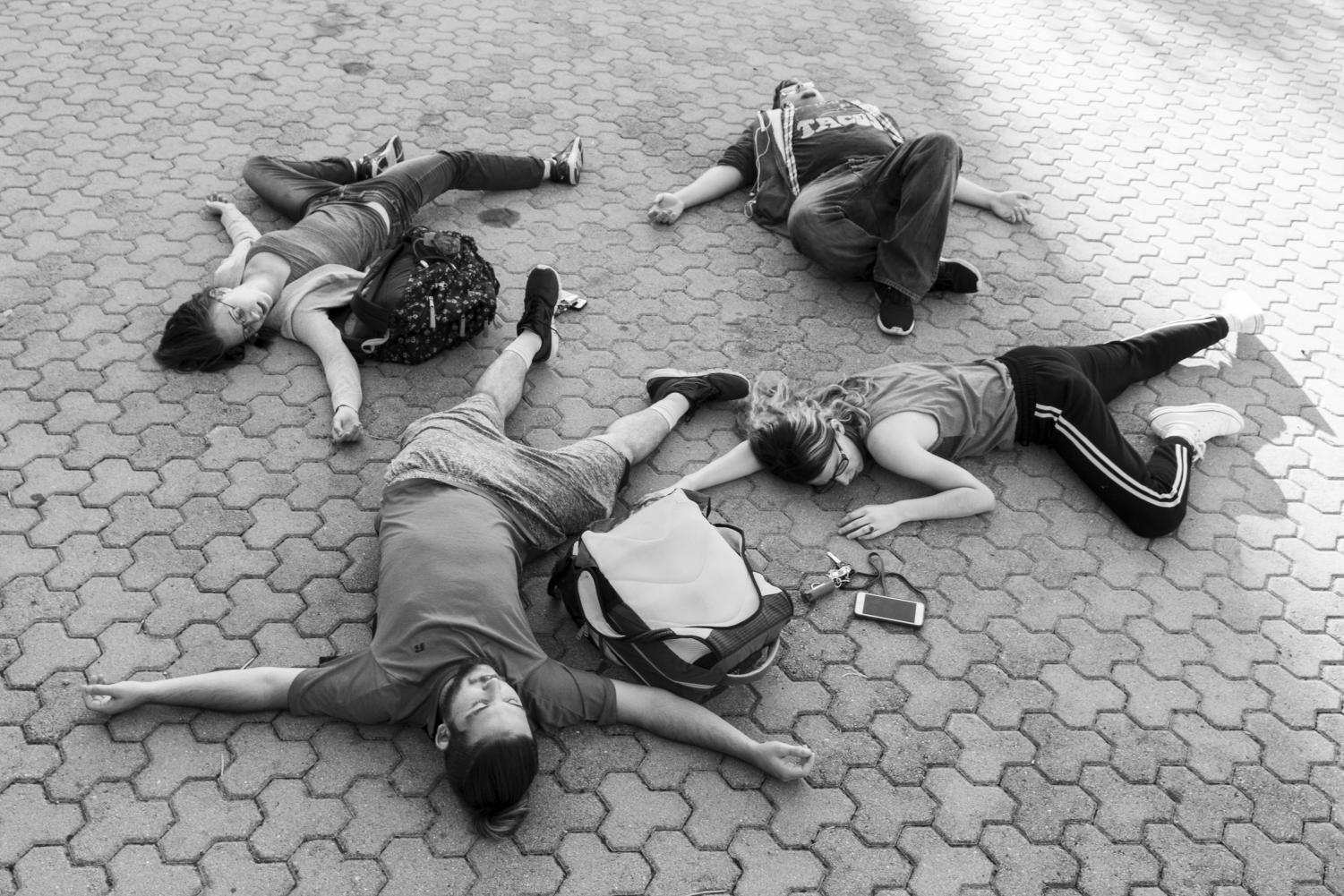 Students play-dead at the base of the Quad after the first few weeks of classes.