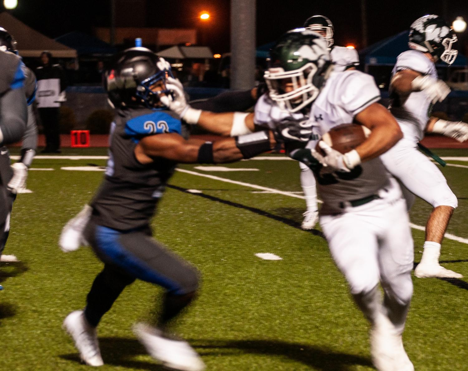 Illinois Wesleyan quarterback fending off a Millikin defender