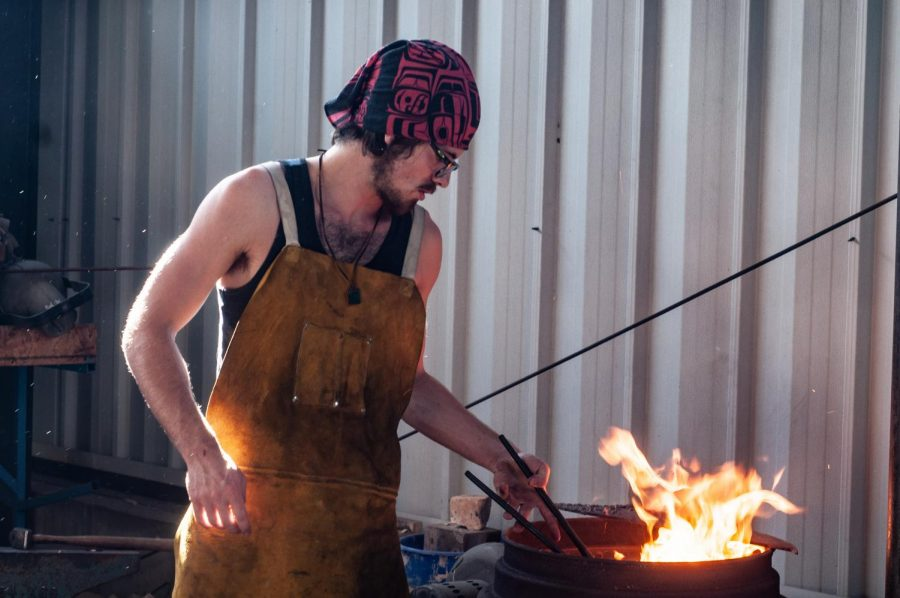 Metal turns red-hot in a primitive forge as sophomore Alex Bergland stokes the flame.