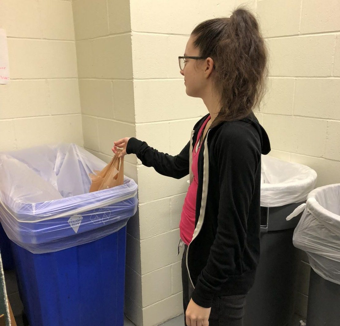 Josie Hand dispenses her recyclables in a proper recycling bin in Dolson Hall - or does she?