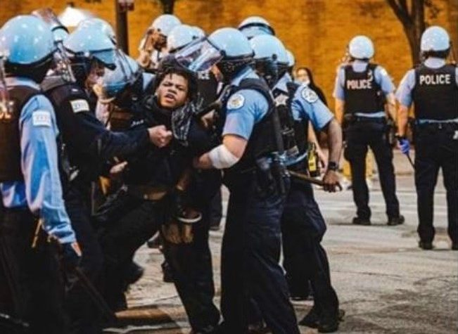 This picture, shared heavily on social media, shows Justin Cosby being forcibly detained by multiple members of the Chicago Police Department.