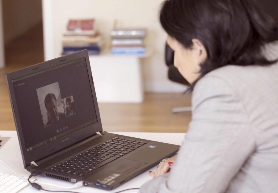 A person is looking at a laptop. They are on a video call with another person.