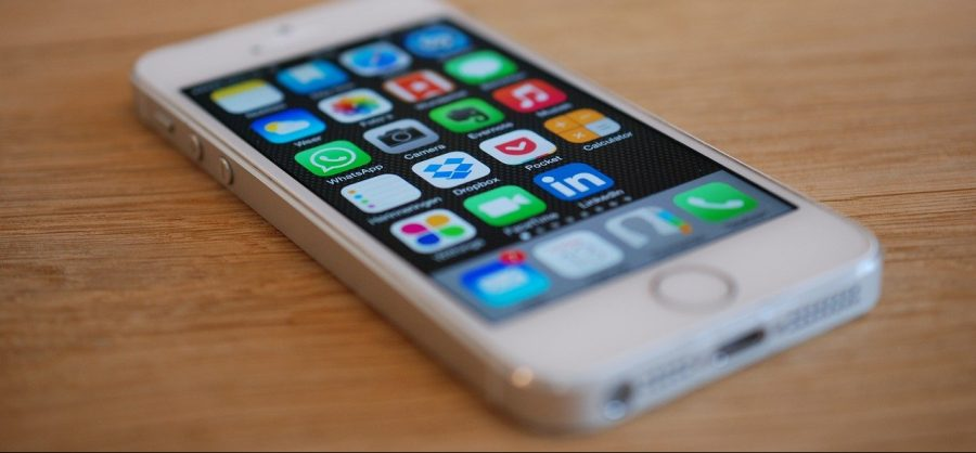 A white iPhone with several apps on the screen.